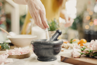A hand adding ingredients to a pestle and mortar on a kitchen counter.  11093009700| 写真素材・ストックフォト・画像・イラスト素材|アマナイメージズ