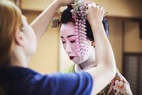 A geisha or maiko with a hair and make up artist creating the traditional hair style and make up. An elaborate flower decoration 11093012196| 写真素材・ストックフォト・画像・イラスト素材|アマナイメージズ
