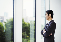 A businessman in the office, by a large window, looking out. 11093012295| 写真素材・ストックフォト・画像・イラスト素材|アマナイメージズ