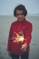 A young girl holding a lighted sparkler on the beach at dusk.