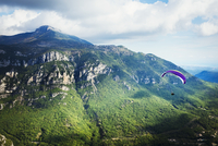 A paraglider in flight over a valley in the mountains. 11093013468| 写真素材・ストックフォト・画像・イラスト素材|アマナイメージズ