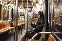 A woman sitting in a metro subway carriage looking at her cellphone. 11093013873| 写真素材・ストックフォト・画像・イラスト素材|アマナイメージズ