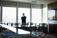 A man standing at a table in a meeting room looking down at an open book. 11093013932| 写真素材・ストックフォト・画像・イラスト素材|アマナイメージズ