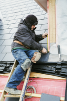 A man at the top of a ladder on a house roof, fixing tiles on a dormer roof. 11093014393| 写真素材・ストックフォト・画像・イラスト素材|アマナイメージズ