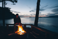Man sitting by campfire at dusk, San Juan Islands in the distance, Washington, USA.