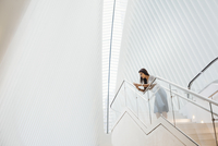 A woman on the stairs leaning on a railing in the vast space of the atrium of the Oculus building at the World Trade Centre site 11093014888| 写真素材・ストックフォト・画像・イラスト素材|アマナイメージズ