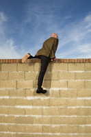 Rear view of man wearing a suit climbing over yellow brick wall. 11093015300| 写真素材・ストックフォト・画像・イラスト素材|アマナイメージズ