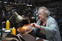 A grey haired senior worker of over 80 years old, a woman sitting at a sewing machine in a shoemaker's workshop. 11093015606| 写真素材・ストックフォト・画像・イラスト素材|アマナイメージズ