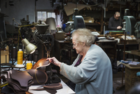 A grey haired senior worker, a woman sitting at a sewing machine in a shoemaker's workshop. 11093015607| 写真素材・ストックフォト・画像・イラスト素材|アマナイメージズ