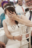 Bride in her wedding dress sitting in a marquee, laughing and covering her face. 11093015760| 写真素材・ストックフォト・画像・イラスト素材|アマナイメージズ