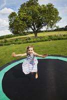 Girl in a sundress jumping on a trampoline in a garden.