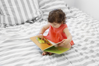 High angle view of baby girl in red dress sitting on bed with stripy duvet, looking at book. 11093016968| 写真素材・ストックフォト・画像・イラスト素材|アマナイメージズ
