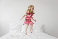 Smiling blond girl wearing red and white checkered dress jumping on bed with white duvet. 11093017157| 写真素材・ストックフォト・画像・イラスト素材|アマナイメージズ