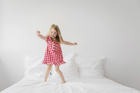 Smiling blond girl wearing red and white checkered dress jumping on bed with white duvet. 11093017158| 写真素材・ストックフォト・画像・イラスト素材|アマナイメージズ