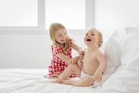 Smiling blond girl wearing red and white checkered dress and baby boy sitting on bed, playing. 11093017161| 写真素材・ストックフォト・画像・イラスト素材|アマナイメージズ