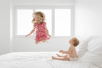 Smiling blond girl wearing red and white checkered dress jumping on bed, baby boy sitting next to her, watching. 11093017162| 写真素材・ストックフォト・画像・イラスト素材|アマナイメージズ