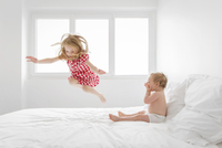 Smiling blond girl wearing red and white checkered dress jumping on bed, baby boy sitting next to her, watching. 11093017163| 写真素材・ストックフォト・画像・イラスト素材|アマナイメージズ