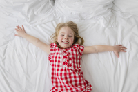 High angle view of smiling blond girl wearing red and white checkered dress lying on bed. 11093017169| 写真素材・ストックフォト・画像・イラスト素材|アマナイメージズ