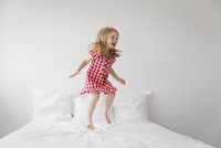 Smiling blond girl wearing red and white checkered dress jumping on bed with white duvet. 11093017179| 写真素材・ストックフォト・画像・イラスト素材|アマナイメージズ