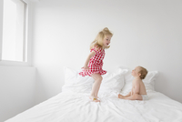 Smiling blond girl wearing red and white checkered dress jumping on bed, baby boy sitting next to her, watching. 11093017180| 写真素材・ストックフォト・画像・イラスト素材|アマナイメージズ