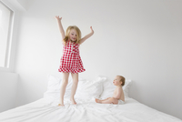 Smiling blond girl wearing red and white checkered dress jumping on bed, baby boy sitting next to her, watching. 11093017181| 写真素材・ストックフォト・画像・イラスト素材|アマナイメージズ