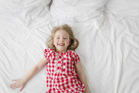 High angle view of smiling blond girl wearing red and white checkered dress lying on bed. 11093017183| 写真素材・ストックフォト・画像・イラスト素材|アマナイメージズ