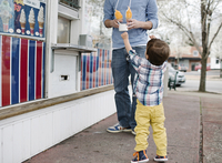 Man and young boy with brown hair wearing checkered shirt, standing on pavement at ice cream stall, holding ice cream cone. 11093017458| 写真素材・ストックフォト・画像・イラスト素材|アマナイメージズ
