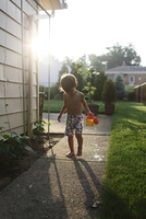 Young boy wearing swimming shorts standing outdoors on paving slabs in a garden, holding yellow plastic watering can. 11093017584| 写真素材・ストックフォト・画像・イラスト素材|アマナイメージズ