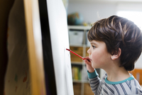 Close up of young boy with brown hair standing at an easel, drawing. 11093017591| 写真素材・ストックフォト・画像・イラスト素材|アマナイメージズ