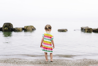 Rear view of young girl wearing striped summer dress standing on a sandy beach, watching ocean. 11093017713| 写真素材・ストックフォト・画像・イラスト素材|アマナイメージズ