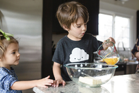 Young girl with green ribbon in her hair standing in a kitchen, watching young boy pouring eggs into glass mixing bowl. 11093017943| 写真素材・ストックフォト・画像・イラスト素材|アマナイメージズ