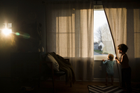 Two children, a boy and a baby girl looking out of a window. 11093018199| 写真素材・ストックフォト・画像・イラスト素材|アマナイメージズ
