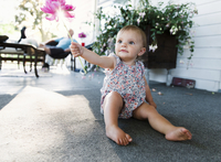 Baby girl sitting on house porch holding up a flower. 11093018348| 写真素材・ストックフォト・画像・イラスト素材|アマナイメージズ
