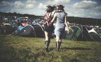 Rear view of two young women at a summer music festival wearing feather headdresses, walking arm in arm towards tents. 11093018760| 写真素材・ストックフォト・画像・イラスト素材|アマナイメージズ