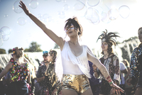 Young woman at a summer music festival wearing golden sequinned hot pants, dancing among the crowd. 11093018788| 写真素材・ストックフォト・画像・イラスト素材|アマナイメージズ
