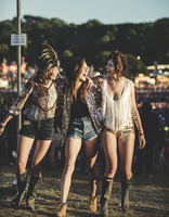 Three young women at a summer music festival wearing hot pants and Wellington boots, feather headdress and faces painted, arms a 11093018814| 写真素材・ストックフォト・画像・イラスト素材|アマナイメージズ