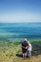 Rear view of elderly couple standing with arms around shoulders looking out to sea across the vivid clear blue water. 11093019133| 写真素材・ストックフォト・画像・イラスト素材|アマナイメージズ