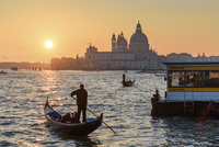 Two gondoliers on the Canale Grande in Venice, Italy, at sunrise, with the dome of Santa Maria della Salute in the distance. 11093019451| 写真素材・ストックフォト・画像・イラスト素材|アマナイメージズ