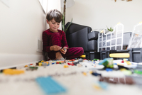 Boy with brown hair wearing stripy red pyjamas sitting on the floor, playing with toy building bricks. 11093019685| 写真素材・ストックフォト・画像・イラスト素材|アマナイメージズ