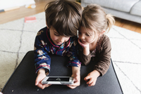 High angle view of boy and young girl lying indoors on their front, looking at smartphone. 11093019695| 写真素材・ストックフォト・画像・イラスト素材|アマナイメージズ