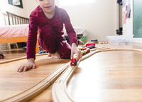Boy wearing stripy red pyjamas kneeling on hardwood floor, playing with wooden toy train. 11093019709| 写真素材・ストックフォト・画像・イラスト素材|アマナイメージズ