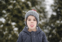 Boy wearing grey knit hat standing outdoors in the snow, looking at camera, sticking out tongue. 11093019742| 写真素材・ストックフォト・画像・イラスト素材|アマナイメージズ