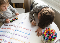 High angle view of boy and young girl sitting indoors at a table drawing with colouring pens. 11093019775| 写真素材・ストックフォト・画像・イラスト素材|アマナイメージズ