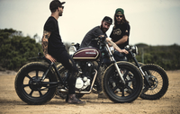 Three men wearing baseball caps and sunglasses sitting on cafe racer motorcycles on a dusty dirt road. 11093019850| 写真素材・ストックフォト・画像・イラスト素材|アマナイメージズ