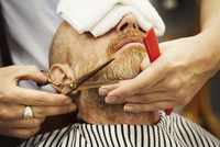 A customer sitting in the barber's chair, with a hot towel on his face, and a barber trimming his beard. 11093022283| 写真素材・ストックフォト・画像・イラスト素材|アマナイメージズ