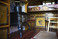A cast iron stove with large metal kettle, a mantlepiece and storage cupboards and raised bed, the interior of a gypsy caravan, 11093022361| 写真素材・ストックフォト・画像・イラスト素材|アマナイメージズ