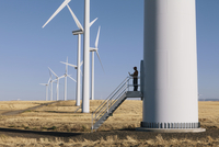A wind farm technician standing and using a laptop at the base of a turbine on a wind farm in open countryside at Palouse. 11093022373| 写真素材・ストックフォト・画像・イラスト素材|アマナイメージズ