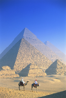 Two people on camels in front of Egyptian pyramids. 11093022894| 写真素材・ストックフォト・画像・イラスト素材|アマナイメージズ