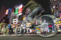 Surface view of cyclists driving on urban street at night illuminated skyscrapers and neon advertising. 11093023163| 写真素材・ストックフォト・画像・イラスト素材|アマナイメージズ