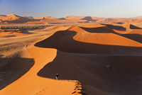 Aerial view of desert landscape, distant view of person walking along ridge of sand dune. 11093023220| 写真素材・ストックフォト・画像・イラスト素材|アマナイメージズ